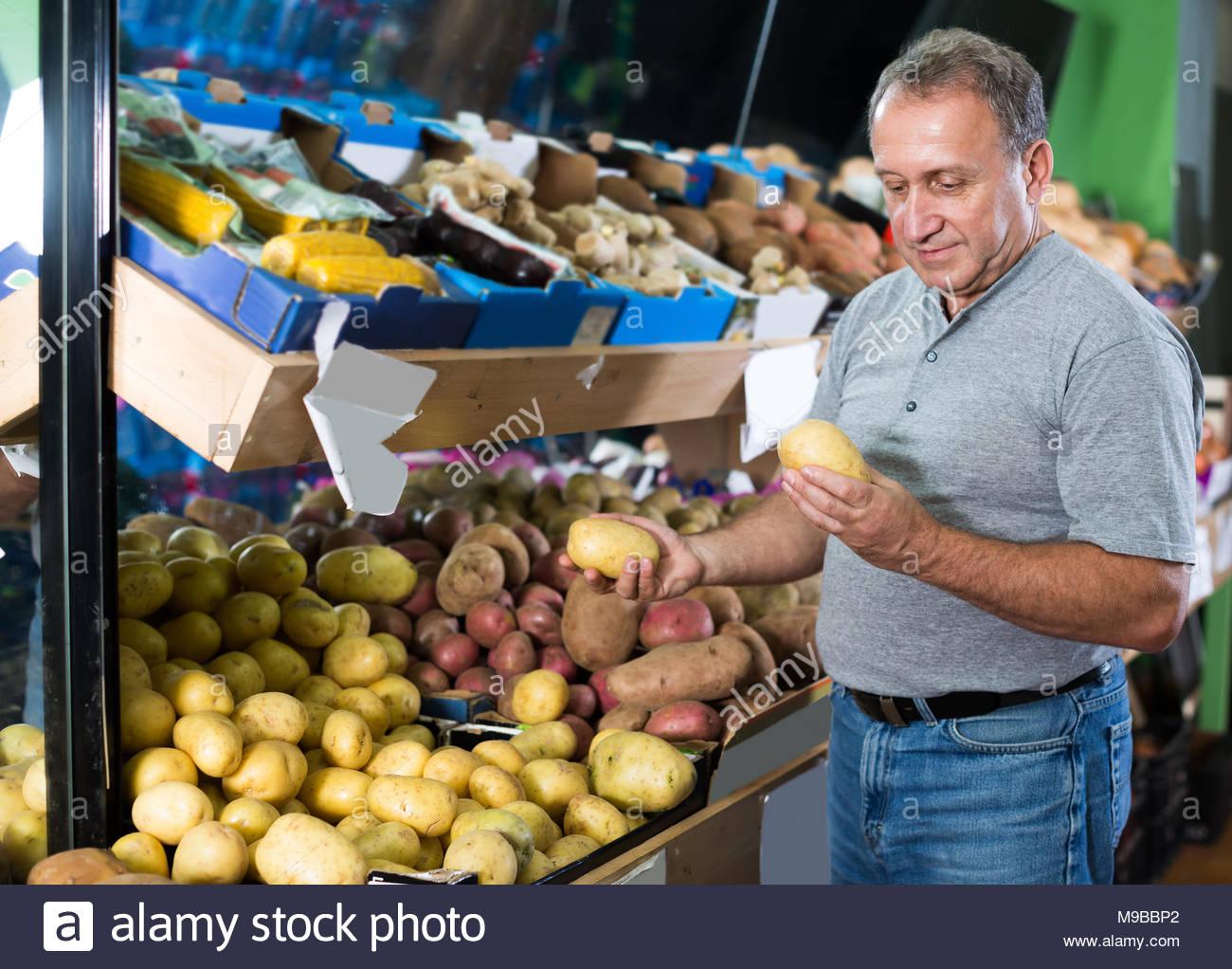 glad-man-is-choosing-potato-in-the-vegetables-store-M9BBP2.jpg